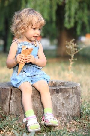 Child with ice-cream sitting on stump