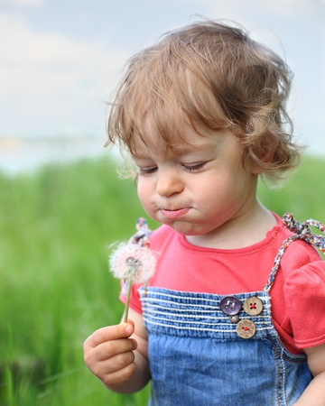 Beautiful child blows on dandelion in the summer. Shallow depth of field photo