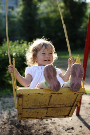 Playing on the swings after summer rain - shallow depth of field, back lighting   Stock Photo - 8786033
