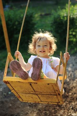 columpio: Linda ni�a jugando en los vaivenes Foto de archivo