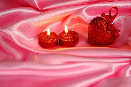 Valentine`s heart and two candles on pink satin. Shallow depth of field photo