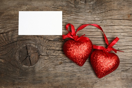 Valentine`s card blank and two hearts on old wood photo