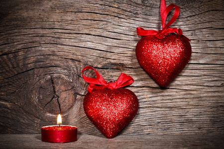 burning love: Two hearts and burning candle on old wood Stock Photo