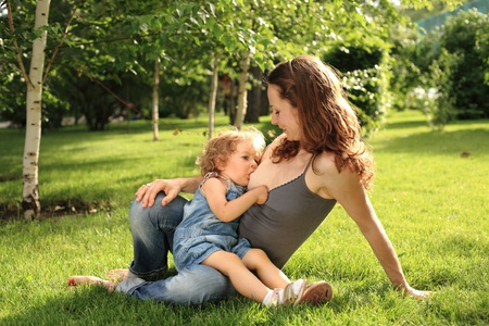 breastfeed: Cute woman nurses her little child in park. Shallow depth of field