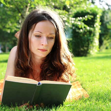 Cute woman reading book in summer park photo