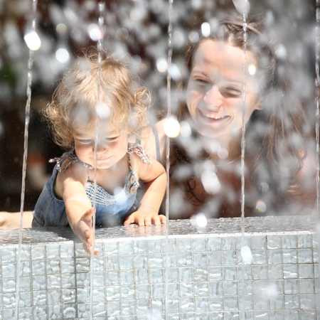 caucasian water drops: Smiling child and woman in fountain splashes Stock Photo