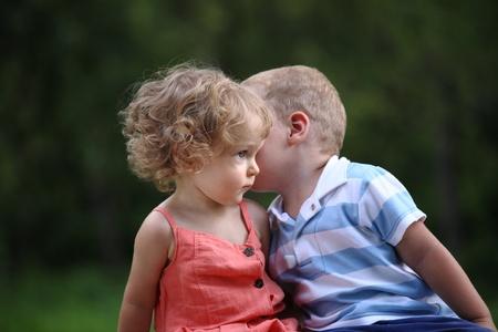 Little boy whispers to lovely girl on ear photo