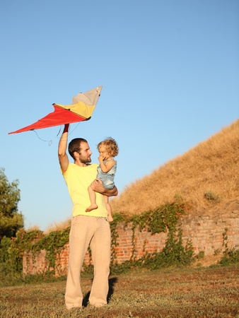Father with child flying a kite photo