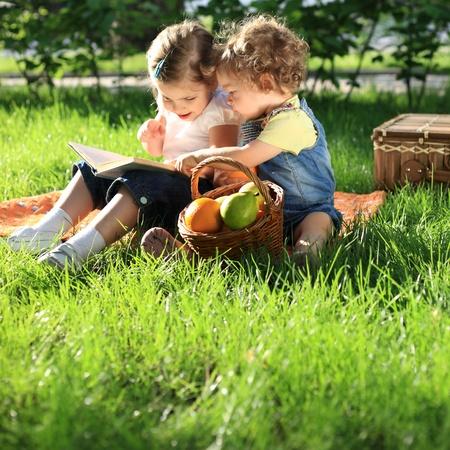ni�os comiendo: Ni�os leyendo el libro de picnic en un parque de verano Foto de archivo
