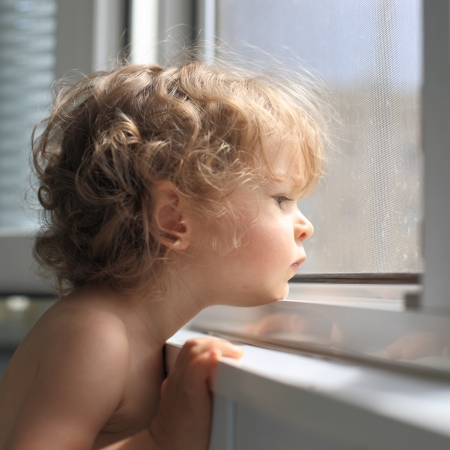 Sad child looking out of the window photo