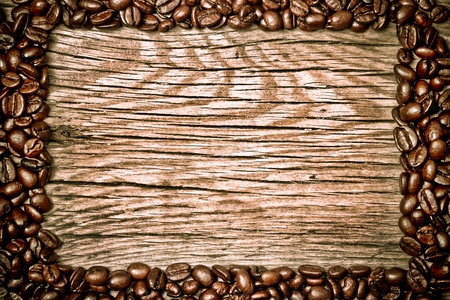 Coffee beans on brown wood texture photo