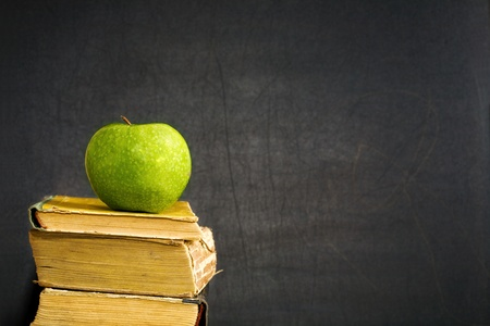 copyspace: Green apple on old textbook against blackboard with copyspace