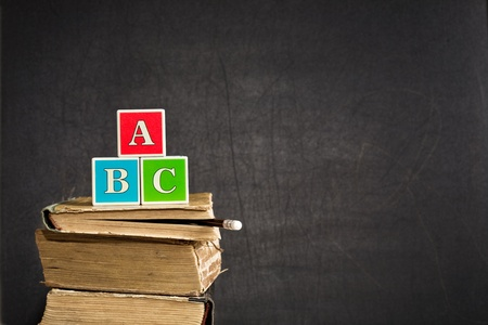 ABC on old textbooks against blackboard in classroom photo