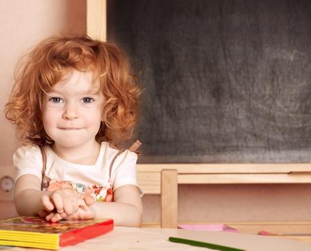 kids learning: Funny smiling schoolchild in a class against blackboard