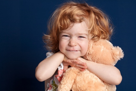 Smiling beautiful child embraces teddy bear photo