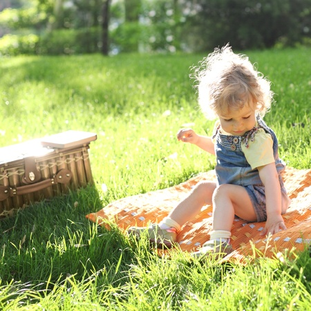 Beautiful child sitting on grass in summer park Stock Photo - 9531636