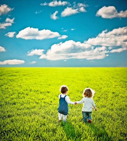 Rear view for two children going on summer field Stock Photo - 9531651