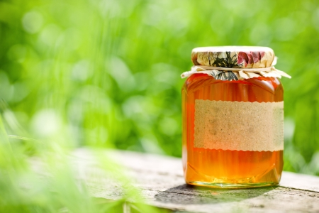 Honey jar on table against nature background photo