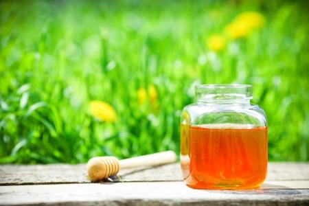 Tarro de miel en la tabla con fondo de naturaleza Foto de archivo
