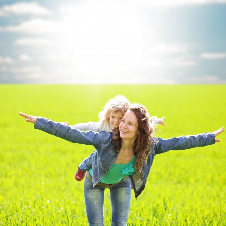 Woman with child having fun in summer field photo