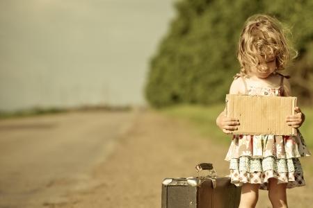 verdrietig meisje: Eenzaam meisje met koffer permanent over road en papier met copyspace bedrijf in handen Stockfoto