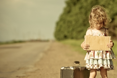 waiting girl: Lonely girl with suitcase standing about road and holding paper with copyspace in hands