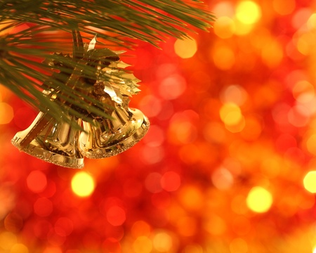 Gold Christmas bells on pine bough photo