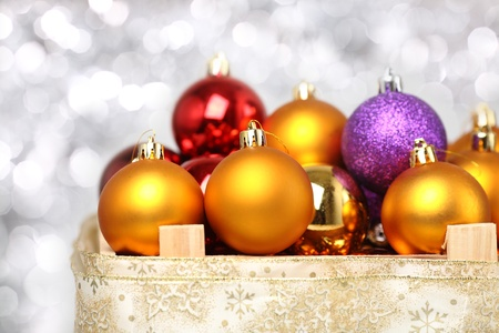 Multicolored Christmas balls on blurred silver background photo