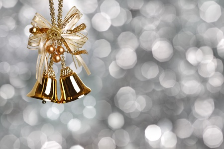 Gold Christmas bells on silver blurred background photo