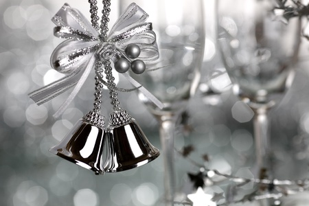 Christmas bells and two empty wineglass on silver background - shallow depth of field photo