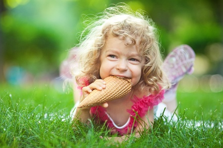 brigth: Smiling child eating ice-cream in summer park Stock Photo