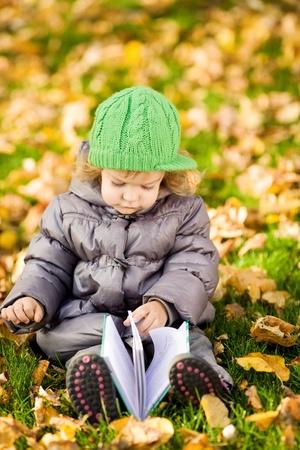 Child reading book in autumn park Stock Photo - 9978574