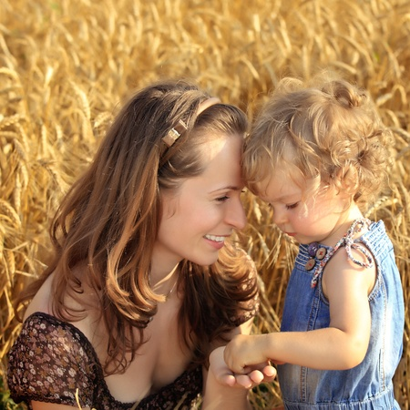 Woman with child in autumn field of wheat photo