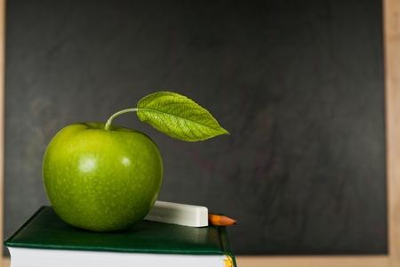 cartilla: Manzana verde con la hoja contra la pizarra en clase. Escuela de concepto