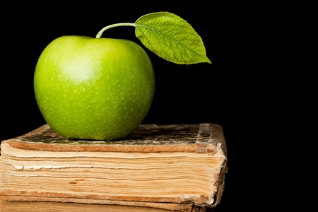 Green apple with leaf on old book isolated on black background. School concept photo