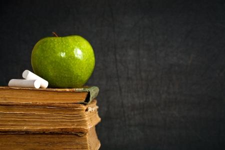 cartilla: Tiza y verde manzana en antiguo libro contra la pizarra en clase. Concepto de escuela