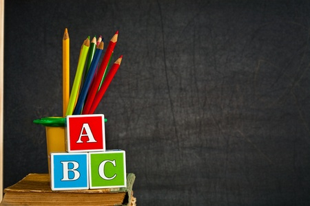 ABC and multicolored pencil on old textbook against blackboard in class. School concept photo