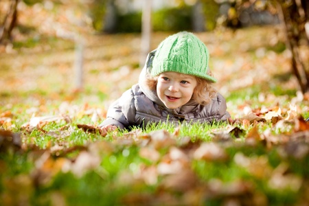 Happy baby girl laying on yellow leaves in autumn park photo