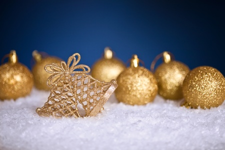 gold christmas tree decorations in snow on blue background stock photo 10105626