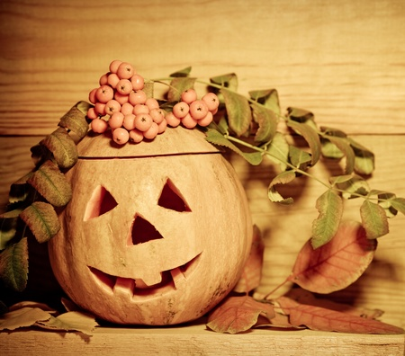 Handmade Halloween pumpkin on wooden background. Autumn holidays concept photo