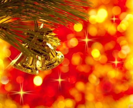 Gold Christmas tree decorations on lights red background photo