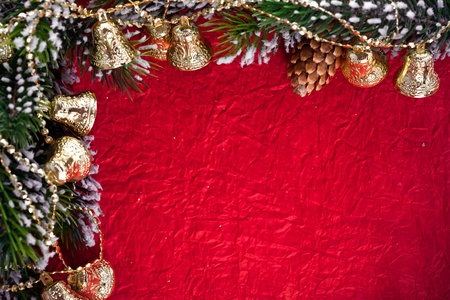 Christmas frame from branch and bells on red paper background Stock Photo - 10425382