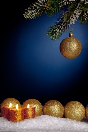 Gold Christmas tree decorations and candles in snow on blue background photo