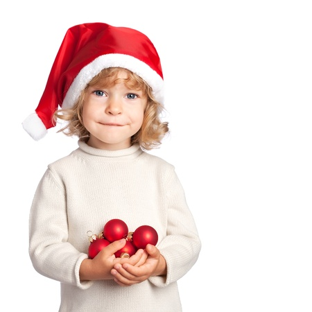 balls kids: Smiling child in Santa hat holding Christmas decorations in hand isolated on white background Stock Photo