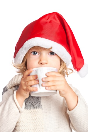 Child in Santa hat drinking hot chocolate. Christmas concept; isolated on white background photo
