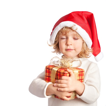 make a gift: Beautiful baby making a wish with Christmas gift box. Isolated on white background Stock Photo
