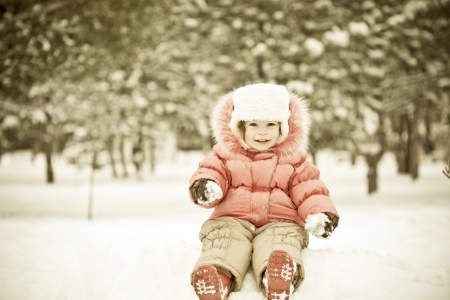 Child playing at snowballs in winter park Stock Photo - 10619987