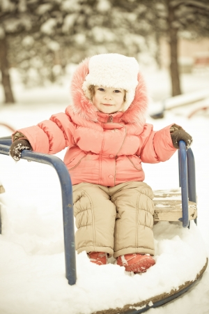 Beautiful baby playing on snow in winter park. Full length portrait, vintage toned photo