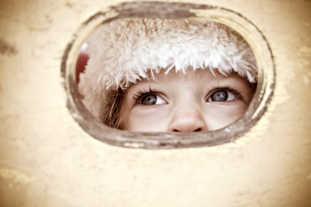 Child look out of hole in wooden background. Shallow depth of field photo