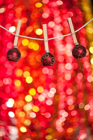 Christmas tree decorations by a rope on lights background photo